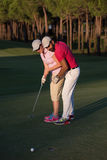 Golf instructions. Male golf instructor teaching female golf player, personal trainer giving lesson on golf course Royalty Free Stock Images