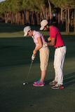 Golf instructions. Male golf instructor teaching female golf player, personal trainer giving lesson on golf course Royalty Free Stock Photos