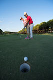 Golf instructions. Male golf instructor teaching female golf player, personal trainer giving lesson on golf course Stock Photo
