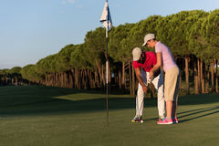 Golf instructions. Male golf instructor teaching female golf player, personal trainer giving lesson on golf course Stock Photography