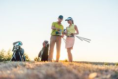 Golf instructor teaching a young woman how to use different golf clubs. Low-angle view of a skilled golf instructor teaching a young women how to use different royalty free stock photo