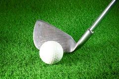 Golf iron and golf ball. On green grass Stock Photos