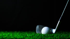 Golf iron and golf-ball on green grass royalty free stock images