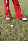 Golf Legs. Male Golf legs in red trouses with brown and white shoes, golf club and ball Royalty Free Stock Image