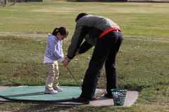 Golf lesson. Young female golfer receiving a golf lesson Royalty Free Stock Images
