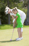 Golf Lesson. Full length viewing of young mother giving golf lesson to daughter royalty free stock photo