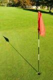 Golf-Loch auf einem setzenden Grün Lizenzfreie Stockfotos
