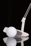 Golf los equipos del putter y del oro en la tabla de cristal negra Foto de archivo