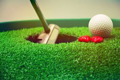 Golf and  with love on green background. Golf and putter are on green grass Royalty Free Stock Images