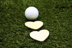 Golf and  with love shape on green background. Golf and wooden heart shapes on green grass, idea for golf lover Stock Photography