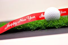 Golf ball Merry X`mas and happy new year sign on green grass