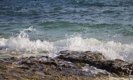 Golf met plons en schuimkamdalingen aan seashore& x27; s steen royalty-vrije stock afbeeldingen