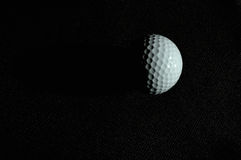 Golf moon. Golf ball was lighted on the dark background looks like a half moon Stock Images