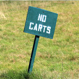 Golf - No Carts Sign. A green No Carts sign with white lettering on a golf course Royalty Free Stock Photo