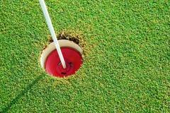 Golf o furo do verde de colocação da prática e identificado por meio de um sinal vermelho Fotos de Stock