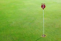 Golf o furo do verde de colocação da prática e identificado por meio de um sinal vermelho Fotografia de Stock Royalty Free