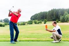 Golf o vídeo da gravação do instrutor do jogador de golfe superior fotografia de stock