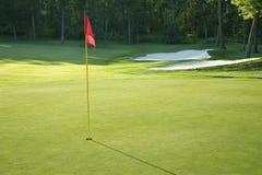 Golf o verde com a bandeira vermelha na luz solar do fim da tarde fotografia de stock royalty free