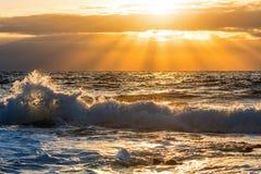 Golf onder een oranje zon bij zonsondergang royalty-vrije stock foto
