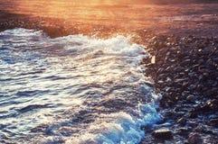 Golf op de zeekust bij zonsondergang royalty-vrije stock fotografie