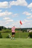 Golf - padre que pone la bola en el hijo que tiende el indicador Fotos de archivo libres de regalías