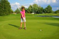 Golf, palla di azionamento del giocatore di golf della ragazza nel foro Immagini Stock