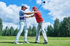 Golf training. Instructor trains new player in summer. Golf play. Instructor explains stroke to new player on green course field training in summer royalty free stock photography