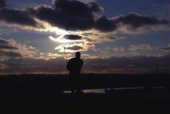 Golf player. Silhouette of golf player with dramatic sunset in background Royalty Free Stock Photo