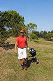 Golf player. Walking with his sticks and golf bag on the fairway Stock Photos