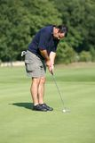 Golf player. Playing a ball in the green Royalty Free Stock Images
