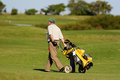 Golf player. Walking with the golf pull cart Stock Photo