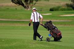 Golf player. Walking with the golf pull cart Royalty Free Stock Image