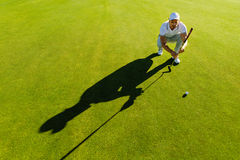 Golf player aiming shot with club on course. Male golfer check line for putting golf ball on green grass Stock Photo