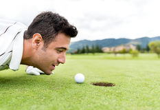 Golf player blowing the ball Stock Images