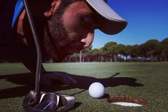 Golf player blowing ball in hole. Concept of cheating and success Stock Photography