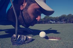 Golf player blowing ball in hole. Concept of cheating and success Stock Image