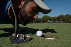 Golf player blowing ball in hole Royalty Free Stock Photos