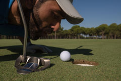 Golf player blowing ball in hole Royalty Free Stock Image