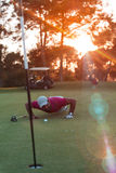 Golf player blowing ball in hole with sunset in background Stock Photos