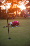 Golf player blowing ball in hole with sunset in background Stock Images
