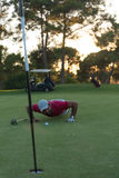 Golf player blowing ball in hole with sunset in background Royalty Free Stock Photos