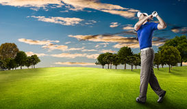 Golf Player. In a blue shirt taking a swing, on a golf course royalty free stock photo