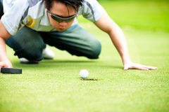 Golf player cheating blowing to get the ball Royalty Free Stock Image