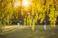 Golf player couple on green. Royalty Free Stock Images