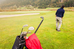 Golf player on the course. A golf player playing on a beautiful golf course and a golf bag full of golf clubs Royalty Free Stock Image