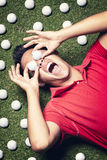 Golf player on floor with balls on eyes. Royalty Free Stock Photo
