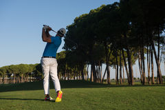 Golf player. Handsome sporty man, golf player hitting shot with club on course at beautiful morning Stock Photography