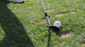 Video: Golf practice at the driving range. A golf player is hiting a golfball that lies on the green grass stock video