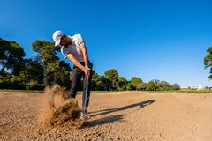 Golf player hits the ball from the bunker and splashes sand royalty free stock image