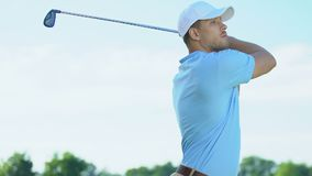 Golf player hitting golf ball from teeing ground on fairway, man practicing stock footage